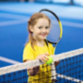 Child playing tennis on indoor court. Li