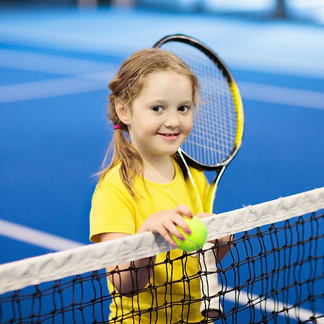 Child playing tennis on indoor court. Li