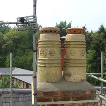 Reclaimed chimney pots installed with terracotta flue vent cappers.