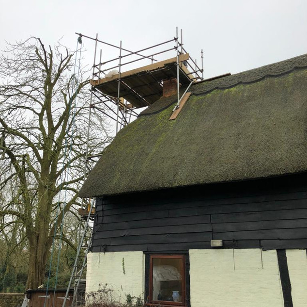Scaffold around a chimney stack on a thatched property.