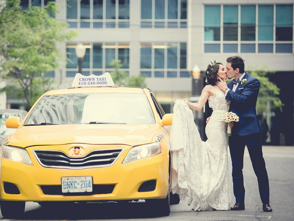 Toronto wedding photographer Little Blue Lemon of Bride and Groom kissing beside an urban yellow cab in Toronto
