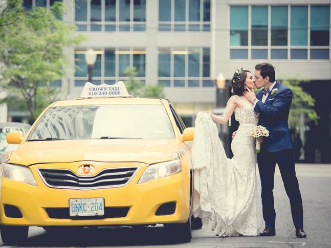 Toronto wedding photographer Little Blue Lemon of Bride and Groom kissing beside an urban yellow cab in Toronto