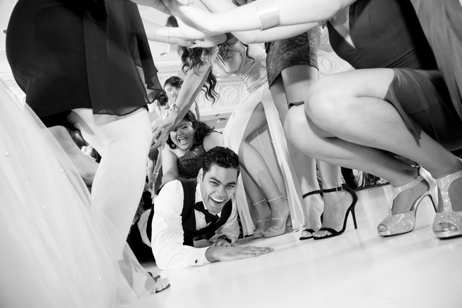 Best wedding photographers Toronto Little Blue Lemon captures groom crawling through ladies legs to get the garter
