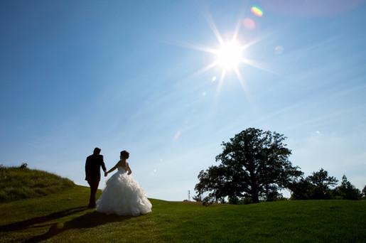 Top wedding photographers Little Blue Lemon captures bride and Groom silhoute against a starburst sun, blue skies