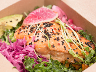 Beautifully prepared pink salmon on a bed of kale in take out container