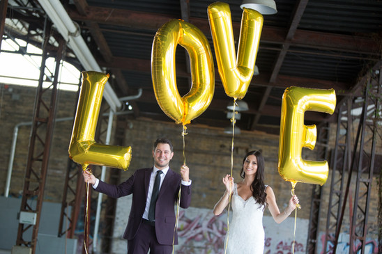 Toronto wedding photographer Little Blue Lemon captures couple holding gold ballons that spell LOVE at Evergreen Brickworks