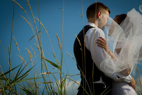 Top wedding photographers Little Blue Lemon captures a couple embracing with a wind whipped veil