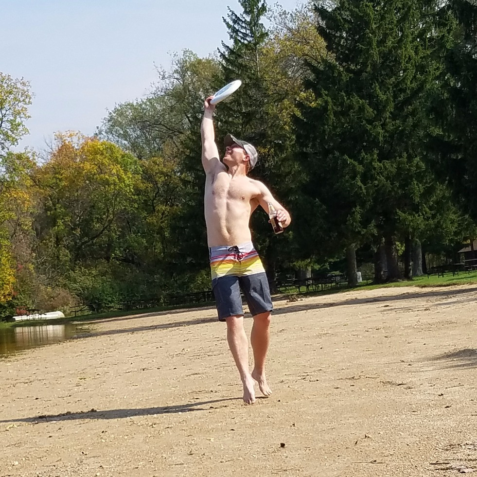 Trevor Paull demonstrating balanced living - an active game of frisbee with a beer in hand
