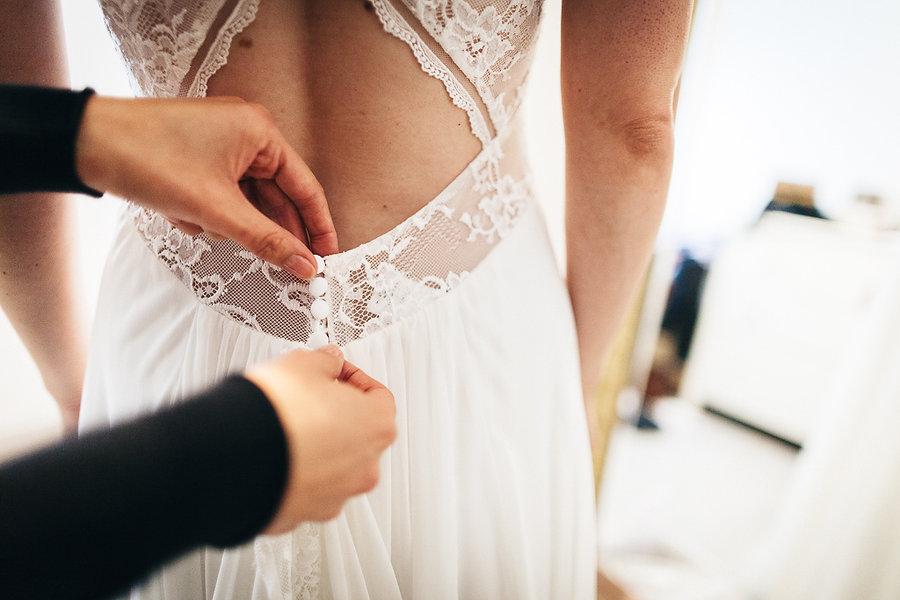 Zuknöpfen des Brautkleids
