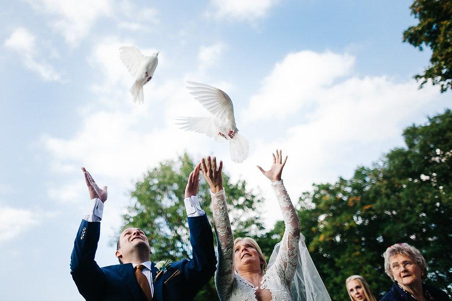 Hochzeitspaar lässt Tauben frei