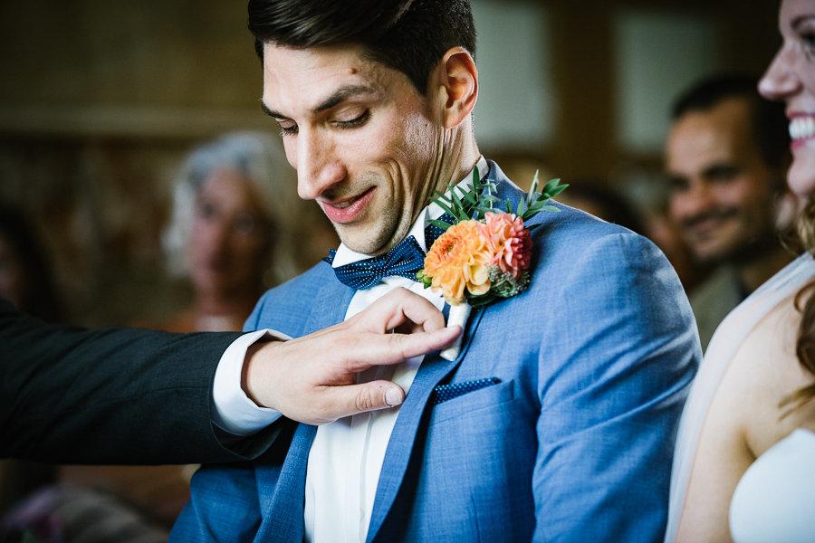 Trauzeeuge richtet dem Bräutigam die Blume