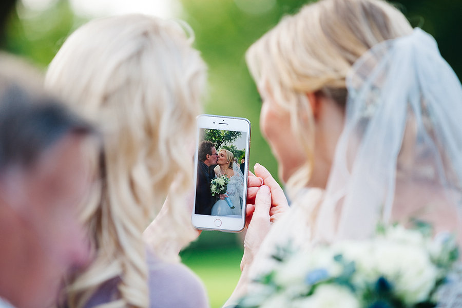 Braut schaut sich Foto auf dem Handy an