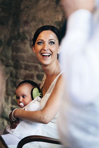 Braut mit Baby und Schallschutzkopfhörer