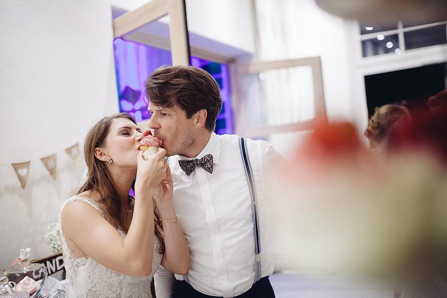 Braut und Bräutigam essen Süßigkeiten auf der Hochzeit