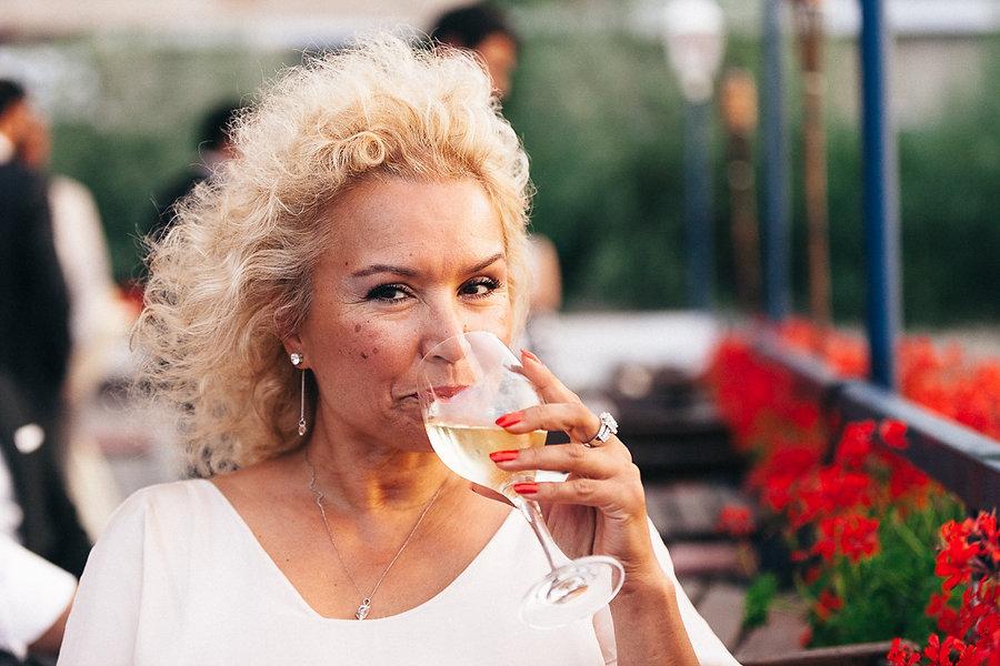 Edle Dame trinkt Wein auf einer Hochzeit