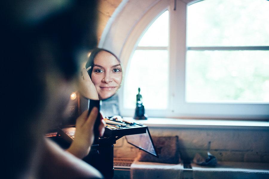 Braut schminkt sich am Spiegel