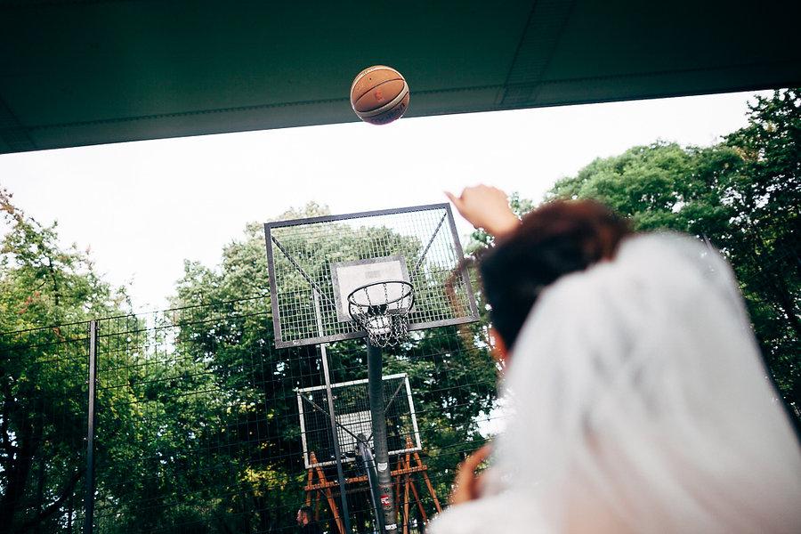 Braut wirft Basketball in einen Korb