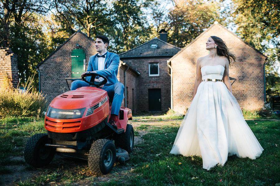 Brautpaar posiert lustig mit einem Bagger