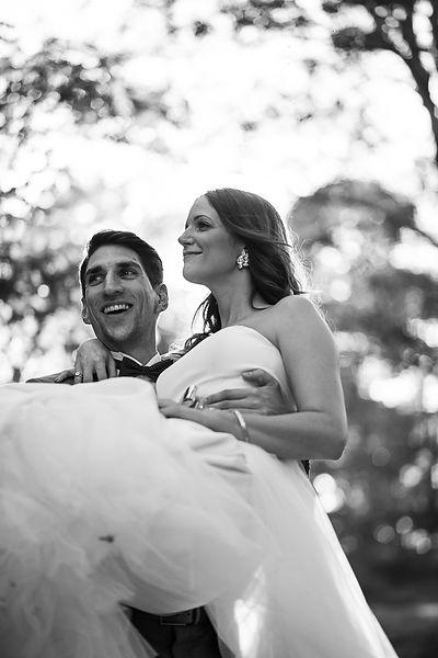 Brautpaar beim Paarshooting. Bräutigam trägt Braut über die Schwelle