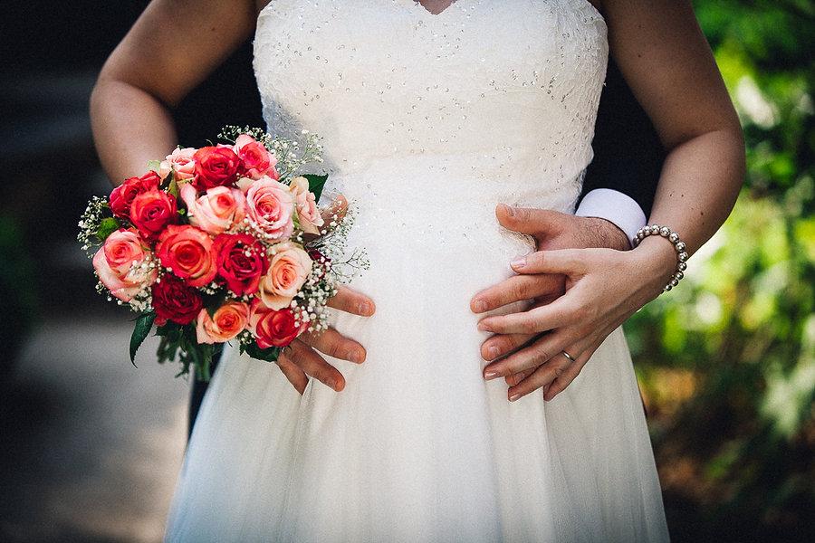 Schwangere Braut und Brautstrauß aus Rosen