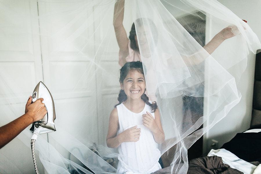 Kind spielt hinter dem Schleier der Braut