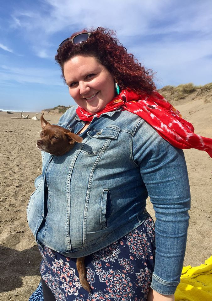 Naomi poses at the beach with her brown chihuahua tucked into her jean jacket. The dog's head sticks out the top of her jacket, and the tail sticks out below.
