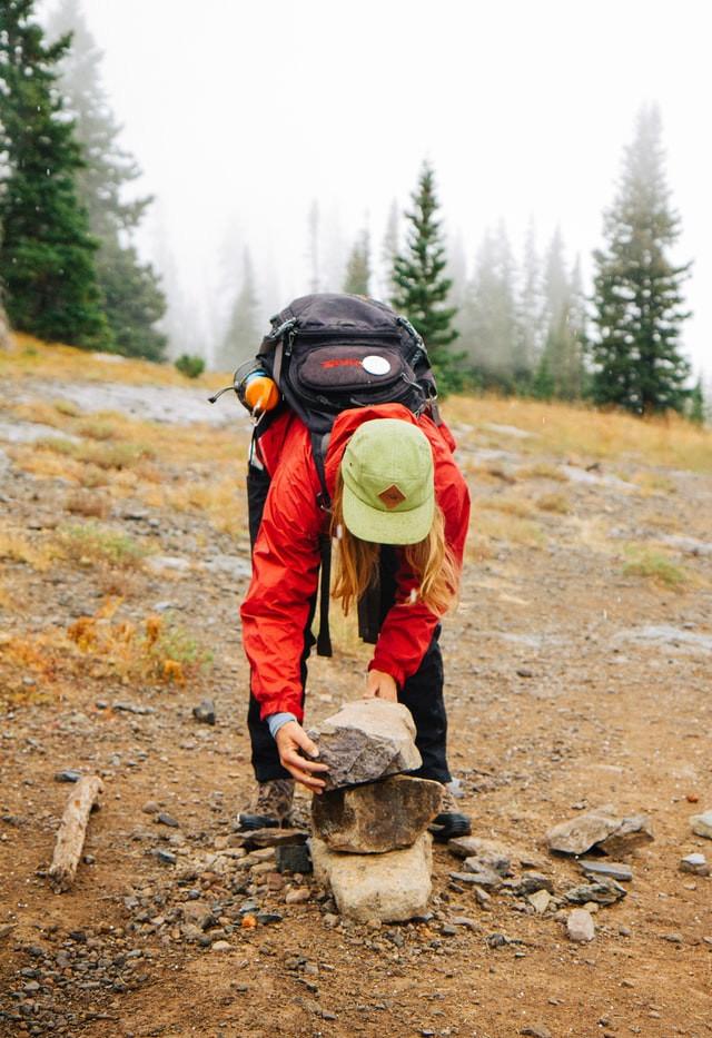 Man picking up rocks wearing a back pack