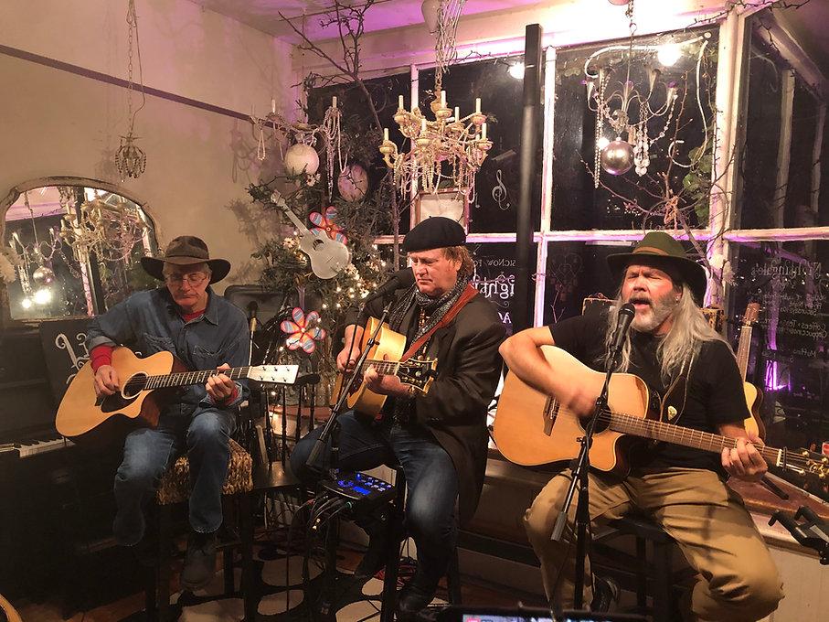 three men playing guitars and singing.jp