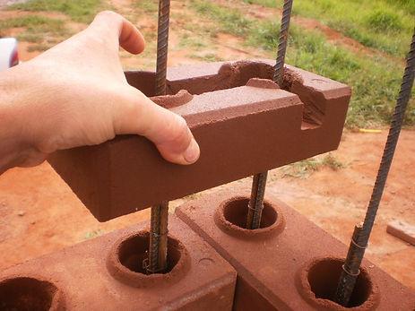 Detalhe de execução do canto de parede com tijolos modulares de solo-cimento, o tijolo ecológico, onde se vê a aplicação da estrutura conjuntamente com a montagem dos tijolos perfurados.