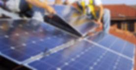 Dois profissionais realizam a instalação de painéis fotovoltaicos de captação de energia do sol sobre o telhado de uma edificação.