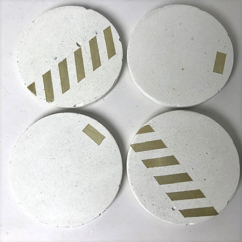 4 white concrete coasters with gold detailing