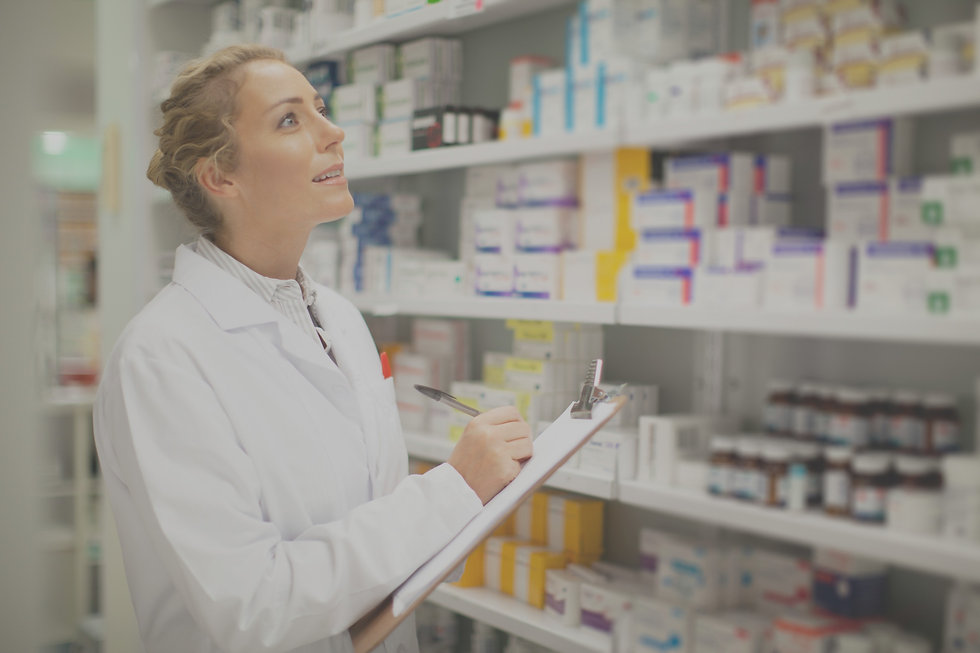 Pharmacist looking at shelves of medication with a clipboard in her hands edited