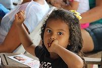 Menina negra, sentada em cadeira em sala de aula olha fixamente para camera.