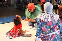 Criança com problemas motores interage com personagens de peça infantil que vestem roupas coloridas.