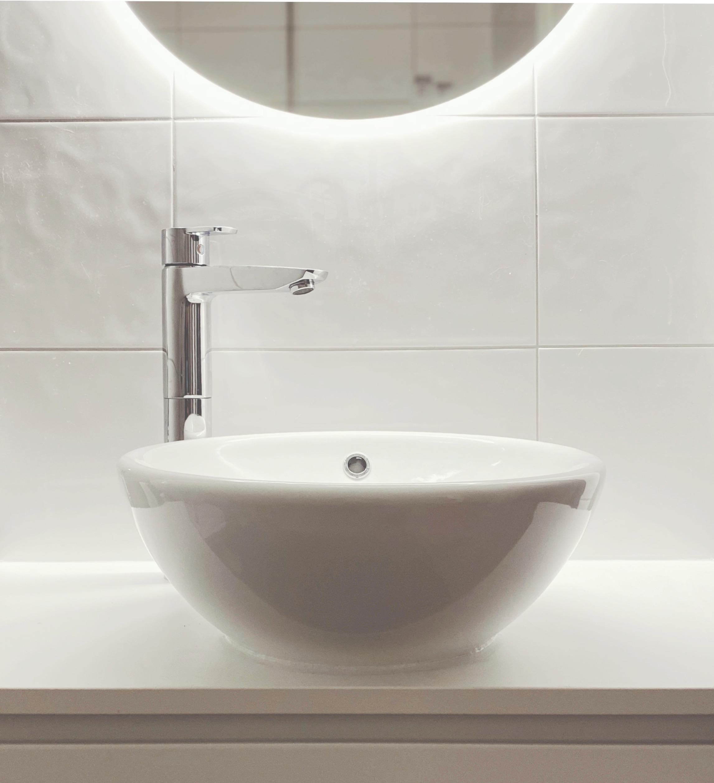 Kylpyhuoneen kasvojenkohotus uudella allastasolla, pesualtaalla ja valopeilillä.