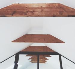 Kylmän ullakkohuoneen muutos asuintilaksi. Kauniit kattoparrut saivat jäädä originelliksi.