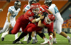 Kahuku running back Harmon Brown (8) barreled into the end zone with help from offensive lineman Vil