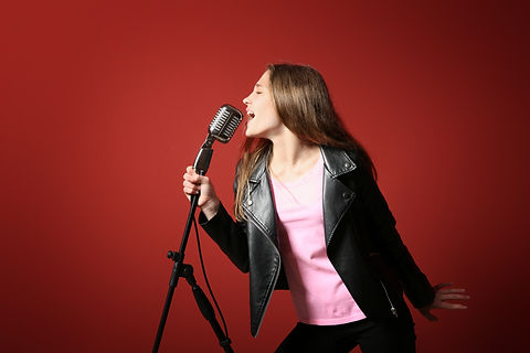 Teenage girl with microphone singing against color background.jpg