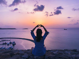 woman-sitting-on-rock-doing-heart-hand-g