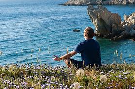 man-sitting-on-flower-fields-facing-ocea