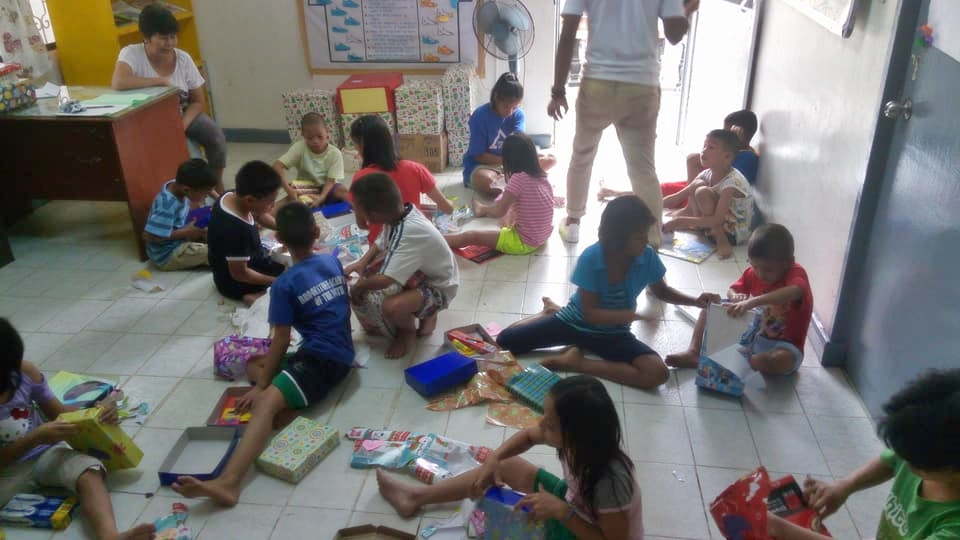 Kids opening their gifts from kind donors.