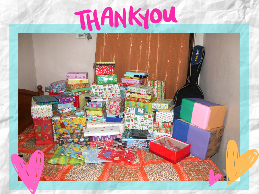 Photo of gifts in a room. Plenty of colorful boxes and a guitar.