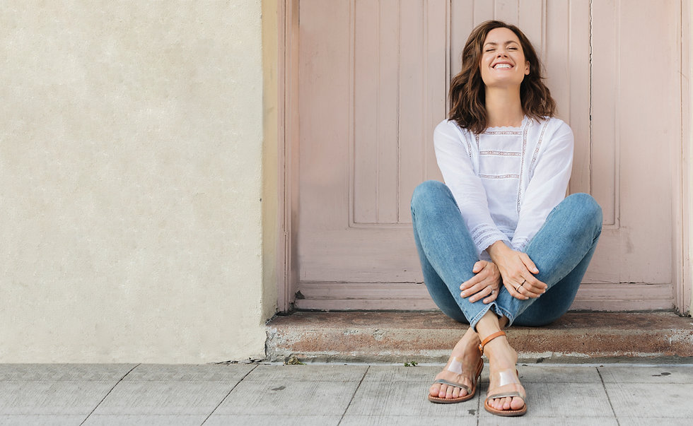 Bridgett Brown sits in front of a pink door with her eyes closed she looks up at the sky smiling