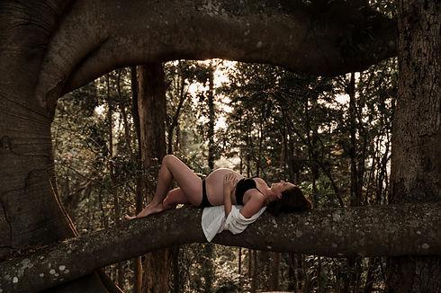 Pregnant woman lying on tree branch