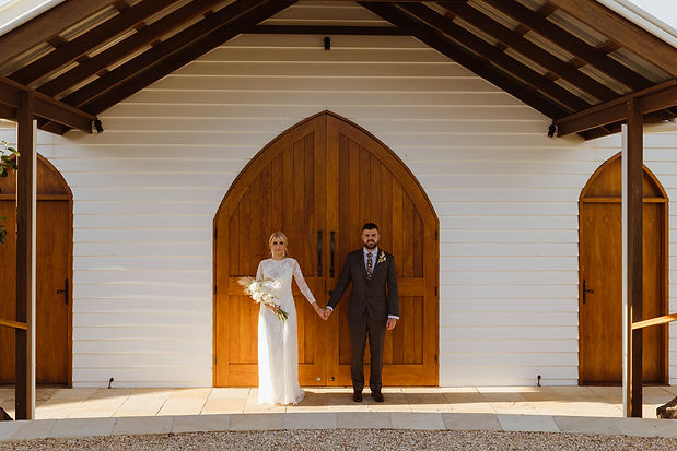 Couple holding hands outside chappel after wedding
