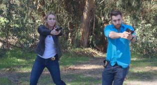 Jim (Austin Fuerst) and Mancini (Erika Young) with guns drawn