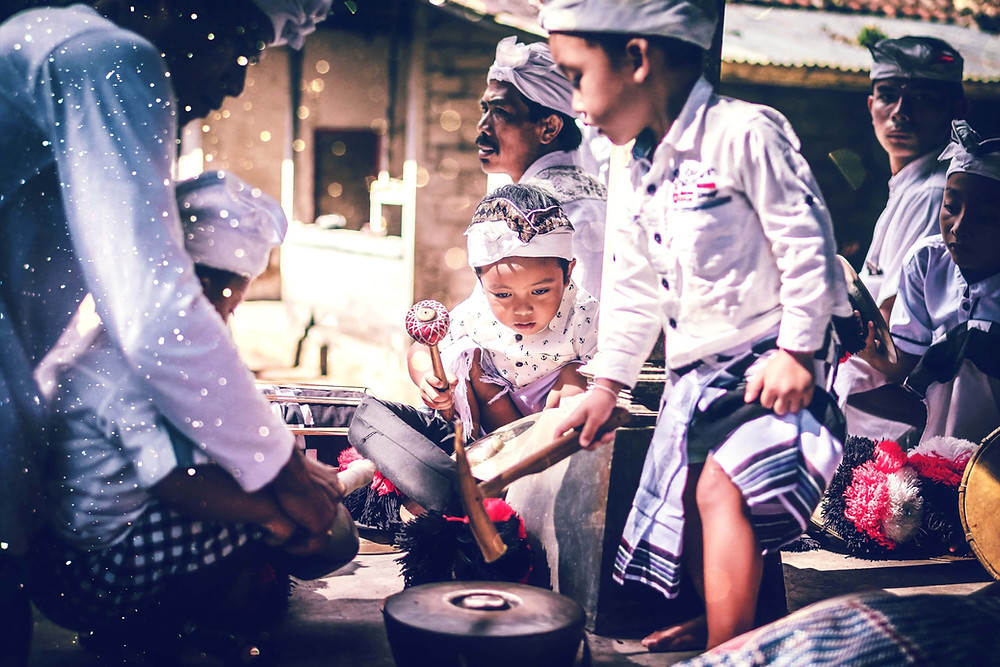 Balinese children playing a drum at a Ceremony wearing traditional clothing