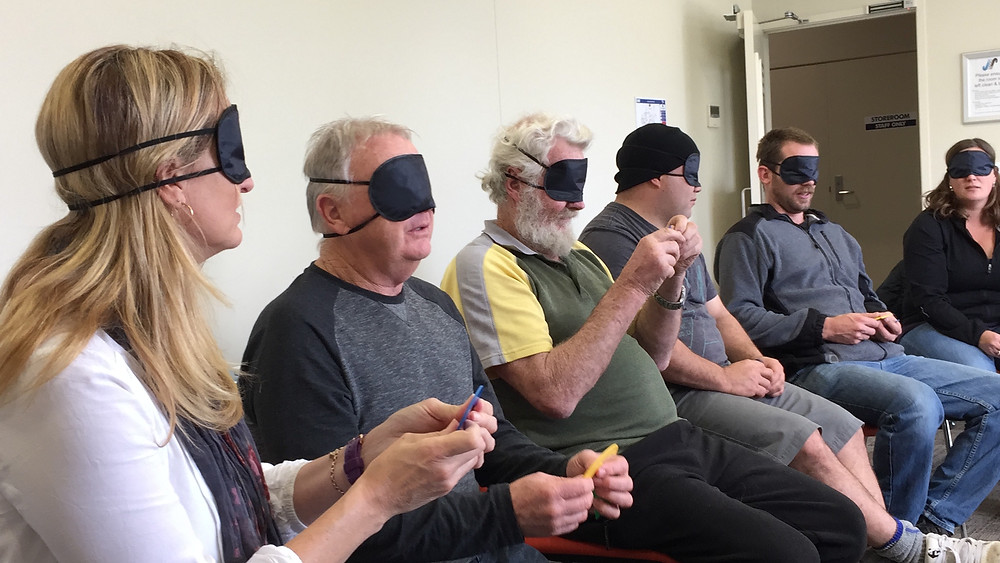 A group of participants playing a game called Colourblind, while blindfolded