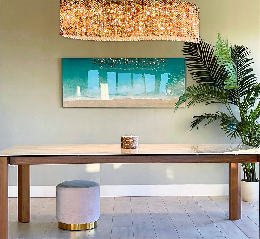 """A large custom artwork hangs above a long dining table and under a golden crystal chandelier. A palm tree is to the right of the art. There is a white and gold stool under the table. a candle sits in the centre of the table. The floor is light bare wood. The artwork is called, """"The Tide Pulls Me Back to Where My Heart Belongs, and was created by Canadian artist, Kimberley Eddy."""