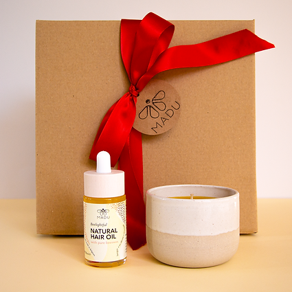 MADUs Christmas box containing natural hair oil and a handbmade beeswax candle
